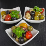 Antipasti salad with tomatoes and olives. Mediterranean antipasti salad with mozzarella balls, green and black olives and cherry tomatoes and some tiny-leafed stock photography