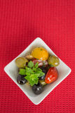Antipasti salad with tomatoes and olives. Mediterranean antipasti salad with mozzarella balls, green and black olives and cherry tomatoes and some tiny-leafed stock photo