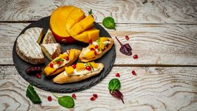 Antipasti snacks. Brushetta with mango, Camembert cheese and pomegranate served on a shale board, rustic wooden table. copy space stock photography
