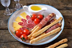 Antipasti snacks - sausage, homemade grissini with jamon, cheese, cherry tomatoes and olive oil. Top view. stock photography