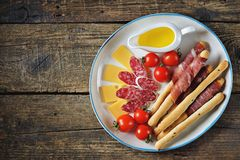 Antipasti snacks - sausage, homemade grissini with jamon, cheese, cherry tomatoes and olive oil. Top view. royalty free stock images