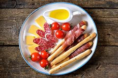 Antipasti snacks - sausage, homemade grissini with jamon, cheese, cherry tomatoes and olive oil. Top view. stock photo