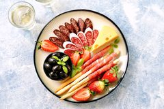 Antipasti snacks - sausage, homemade grissini with jamon, olives, strawberries, capers, cherry tomatoes, white wine, dried tomatoe royalty free stock image