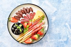 Antipasti snacks - sausage, homemade grissini with jamon, olives, strawberries, capers, cherry tomatoes, white wine, dried tomatoe stock images