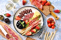 Antipasti snacks - sausage, homemade grissini with jamon, olives, strawberries, capers, cherry tomatoes, white wine, dried tomatoe royalty free stock photo