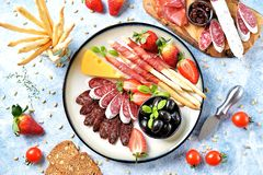 Antipasti snacks - sausage, homemade grissini with jamon, olives, strawberries, capers, cherry tomatoes, white wine, dried tomatoe. S and more. Top view. food stock images