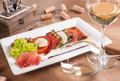 Antipasti with white wine served in a white plate royalty free stock photo