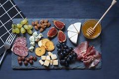 Antipastimatmörker - blått sänker lägger med muttrar, honung, kurerat kött, salami, ostar, druvor och fikonträd royaltyfri fotografi