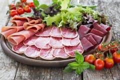 Antipasto με το ζαμπόν, το σαλάμι και το bresaola Ντομάτα και βασιλικός selec Στοκ εικόνες με δικαίωμα ελεύθερης χρήσης