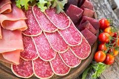 Antipasto με το ζαμπόν, το σαλάμι και το bresaola Ντομάτα και βασιλικός selec Στοκ Φωτογραφίες