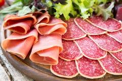 Antipasto με το ζαμπόν, το σαλάμι και το bresaola Ντομάτα και βασιλικός selec Στοκ Φωτογραφία