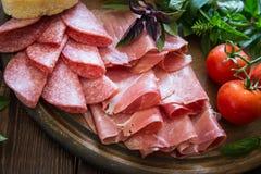 Antipasto με το ζαμπόν, το bresaola και το σαλάμι ψωμί, ντομάτα και βασιλικός Στοκ Φωτογραφία