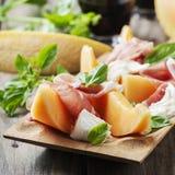 Antipasto με το πεπόνι, τη μοτσαρέλα, το ζαμπόν και το βασιλικό Στοκ εικόνα με δικαίωμα ελεύθερης χρήσης