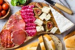 Antipasto Πίνακας ελιών με το σαλάμι, το serrano ζαμπόν, το τυρί, τα καρύδια και το ψωμί ciabatta Στοκ φωτογραφία με δικαίωμα ελεύθερης χρήσης