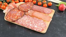 Antipasto appetizers from sliced salami. On wooden board stock video footage