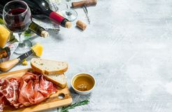Antipasto background. Red and white wine with meat and cheese appetizers. On a rustic background royalty free stock image
