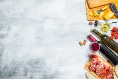Antipasto background. Red and white wine with meat and cheese appetizers. On a rustic background stock photography