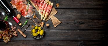 Antipasto background.Various meat appetizer with olives, jamon and red wine stock photos