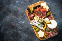 Antipasto board with sliced meat, ham, salami, cheese, olives and red wine. stock image