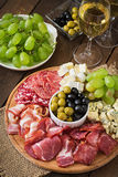 Antipasto catering platter with bacon, jerky, salami, cheese and grapes Stock Images