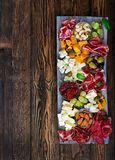 Antipasto catering platter with bacon, jerky, sausage, blue cheese and grapes stock photography