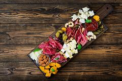 Antipasto catering platter with bacon, jerky, sausage, blue cheese and grapes stock images