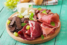 Antipasto catering platter with bacon, jerky, sausage, blue cheese and grapes Stock Image