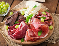 Antipasto catering platter with bacon, jerky, sausage, blue cheese and grapes Stock Photo