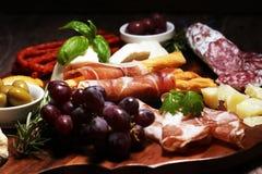 Antipasto divers voorgerecht Scherpe raad met prosciutto, salami, kaas, brood en olijven op donkere houten achtergrond stock foto