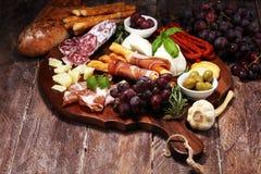 Antipasto divers voorgerecht Scherpe raad met prosciutto, salami, kaas, brood en olijven op donkere houten achtergrond stock foto's