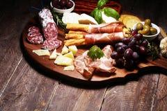 Antipasto divers voorgerecht Scherpe raad met prosciutto, salami, kaas, brood en olijven op donkere houten achtergrond royalty-vrije stock afbeeldingen