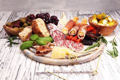 Antipasto divers voorgerecht Scherpe raad met prosciutto, salami, kaas, brood en olijven op witte houten achtergrond stock foto's