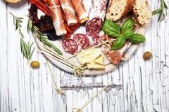 Antipasto divers voorgerecht Scherpe raad met prosciutto, salami, kaas, brood en olijven op witte houten achtergrond stock afbeeldingen