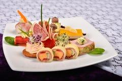 Antipasto et plateau de restauration avec différents apéritifs (fruits, Images stock