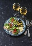 Antipasto et vin méditerranéens de style Saumons fumés, avocat, bruschette d'arugula, olives et deux verres de vin blanc Images libres de droits