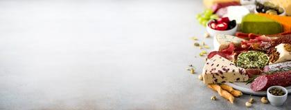 Antipasto italiano tradicional, placa de corte com salame, carne fumado fria, prosciutto, presunto, queijos, azeitonas, alcaparra imagem de stock royalty free