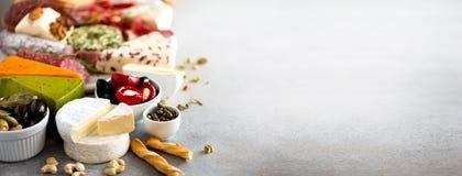 Antipasto italien traditionnel, planche à découper avec le salami, viande fumée froide, prosciutto, jambon, fromages, olives, câp images stock