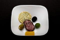 Antipasto-Oliven und Salami Stockfotos