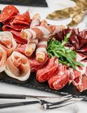 Antipasto platter cold meat with grissini bread sticks, prosciutto, slices ham, beef jerky, salami on slate stone board. Over marble background. Meat appetizer royalty free stock photography