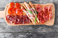 Antipasto platter cold meat plate with grissini bread sticks, prosciutto, slices ham, beef jerky, salami and arugula Royalty Free Stock Image