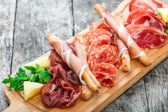 Antipasto platter cold meat plate with grissini bread sticks, prosciutto, slices ham, beef jerky, salami and arugula. On cutting board on wooden background royalty free stock images