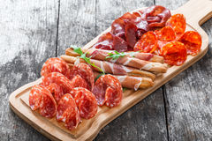 Antipasto platter cold meat plate with grissini bread sticks, prosciutto, slices ham, beef jerky, salami on cutting board. Antipasto platter cold meat plate with stock images