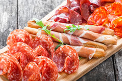 Antipasto platter cold meat plate with grissini bread sticks, prosciutto, slices ham, beef jerky, salami on cutting board Royalty Free Stock Images
