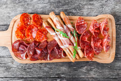 Antipasto platter cold meat plate with grissini bread sticks, prosciutto, slices ham, beef jerky, salami on cutting board Stock Photo