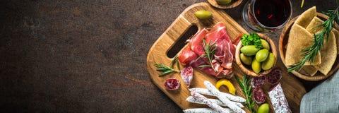 Antipasto pokrojony mięso, baleron, salami, oliwki i wino odgórny widok -, obraz royalty free