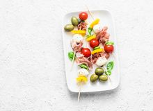 Antipasto skewers. Mediterranean appetizer to wine - prosciutto, bell peppers, cherry tomatoes, mozzarella cheese on skewers. Deli stock photography