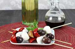 Antipasto skewers of red peppers, mozzarella, garlic and Italian. Antipasto on a skewer.  Skewers include Italian olives, roasted peppers and garlic with Royalty Free Stock Images