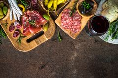 Antipasto - sliced meat, ham, salami, olives on dark stone table top view. royalty free stock image