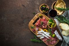 Antipasto - sliced meat, ham, salami, olives and wine top view. stock image