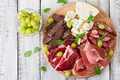 Antipasto som sköter om uppläggningsfatet med bacon, knyckigt, korven, ädelost och druvor Royaltyfri Foto